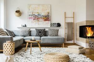 Wooden table next to grey corner settee in warm living room inte